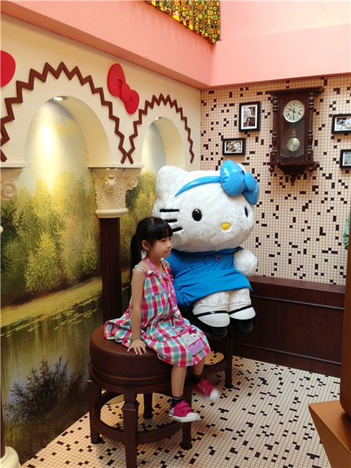 A little girl posing with Hello Kitty in a photo studio. Family portraits are a huge thing in Chinese culture