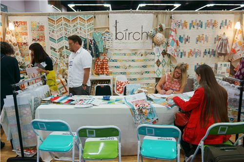 Sandra is ordering fabrics at the birch booth sitting on super cool Pantone chairs