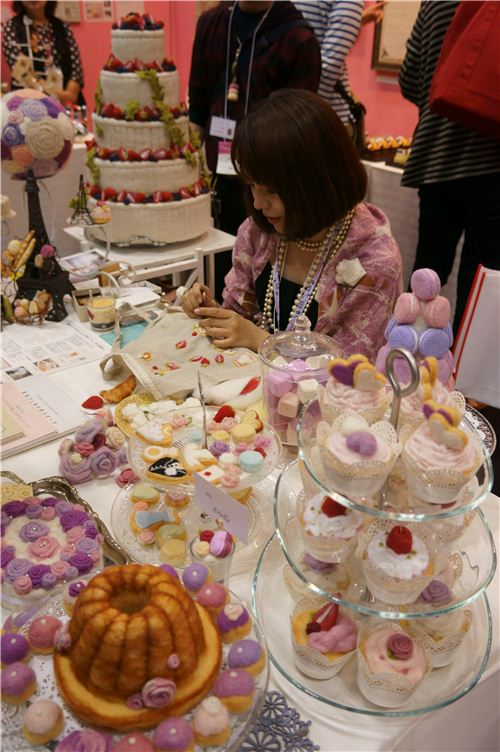 A woman surrounded by clay sweets